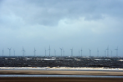 © Licensed to London News Pictures. 27/12/2013. New Brighton, UK A wind farm seen in the Bay of Liverpool during gusty and windy weather on 27th December 2013. It has been reported today 31st December that Energy firms are paid to shut down wind farms during gusty weather as they are unable to cope with the extra production. Photo credit : Stephen Simpson/LNP