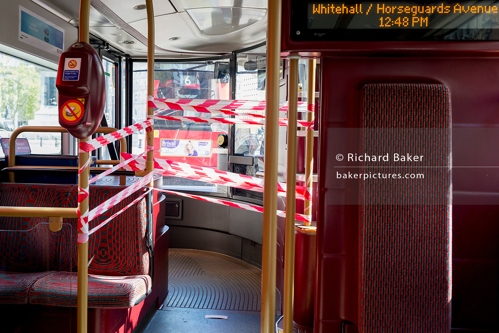 At the beginning of the fourth week of the UK government's lockdown during the Coronavirus pandemic, and with 120,067 UK reported cases with 16,060 deaths, a number 12 bus passes through Whitehall with the front door taped off, a measure that reduces the proximity between bus passengers and drivers after 20 drivers have died from Covid-19 across the country. Passengers embark through middle doors and payment keypads on London buses have been disabled so no fares are currently being taken, on 20th April 2020, in London, England.