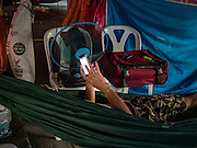 08 DECEMBER 2016 - BANGKOK, THAILAND:  A member of the crew checks his smart phone while he relaxes in a hammock during a Chinese opera (also called ngiew in Thailand) performance at Pek Leng Keng Shrine in the Khlong Toei neighborhood of Bangkok. Public performances of music and celebration were banned during the first 30 days of the mourning period for Bhumibol Adulyadej, the Late King of Thailand. Now, nearly two months after the revered monarch's death, Bangkok street life is returning to normal and Chinese temples and shrines are once again scheduling operas.     PHOTO BY JACK KURTZ