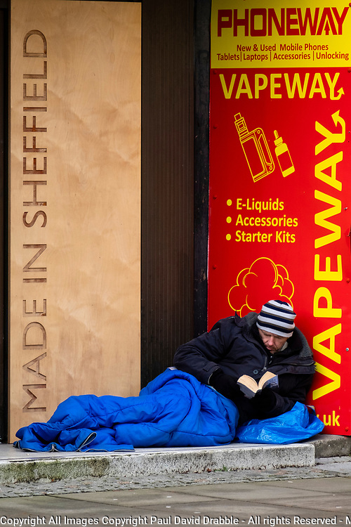 As the third national UK lockdown comes into effect a man lies huddled in a sleeping bag reading a book in the doorway of a closed shop Pinstone street Sheffield opposite the Peace Gardens<br /> <br /> 05 January 2020<br /> <br /> www.pauldaviddrabble.co.uk<br /> All Images Copyright Paul David Drabble - <br /> All rights Reserved - <br /> Moral Rights Asserted -