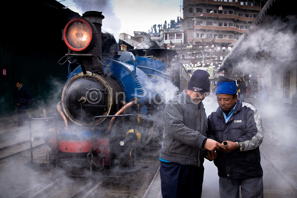 """Train driver Birkh Dattani (right) and his station manager run through standard procedures for the the daily run from Kurseong back to Darjeeling. The Darjeeling Himalayan Railway, nicknamed the """"Toy Train"""", is a narrow-gauge railway from Siliguri to Darjeeling in West Bengal, run by the Indian Railways. It was built between 1879 and 1881 and is about 86 km long. The elevation level is from about 100 m at Siliguri to about 2200 m at Darjeeling. It is still powered by a steam engine and travels daily between the two towns.  It is now classed as a World Heritage Site by UNESCO. India."""