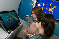 Kendall Boisvert watches as Laurel Normandin disects a cat during a hands on presentation of zSpace an interactive virtual reality computer program at Gilford High School on Wednesday morning.  (Karen Bobotas/for the Laconia Daily Sun)