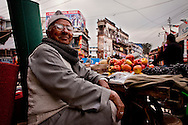 A man sells fruit in a market in Dehradun, India. Like many Asian markets, it is full of fruits, vegetables and some meats and fish.