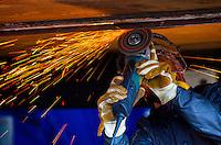 Shipyard worker operates grinder on hull of fishing vessel, in Kodiak, Alaska shipyard.