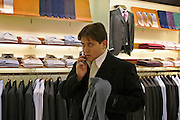 Moscow, Russia, 04/03/2006.&#xA;A young marketing executive takes amobile phone call while trying on clothing in the Zeynoi menswear store, part of the central Moscow complex of luxury stores controlled by the Russian Mercury Group.<br />