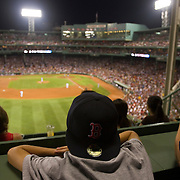 A young man enjoys the view while seated on the Green Monster in left field of Boston Red Sox's Fenway Park.