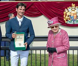 Queen Elizabeth II presents a Rolex watch to Switzerland's Steve Guerdat after he won the Rolex Grand Prix during the Royal Windsor Horse Show at Windsor Castle, Berkshire.
