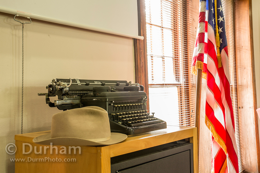 A hat and typewriter representing the journalist of 1925 in the still active yet preserved courtroom in the Rhea County courthouse, in Dayton tennessee where the Scopes trial occured in 1925.. In that year, a high school teacher, John Scopes, was accused of violating Tennessee's Butler Act, which made it unlawful to teach human evolution in any state-funded school. <br /> The trial served its purpose of drawing intense national publicity, as national reporters flocked to Dayton to cover the big-name lawyers who had agreed to represent each side. William Jennings Bryan, three-time presidential candidate for the Democrats, argued for the prosecution, while Clarence Darrow, the famed defense attorney, spoke for Scopes. The trial publicized the Fundamentalist–Modernist Controversy which set modernists, who said evolution was consistent with religion, against fundamentalists who said the word of God as revealed in the Bible took priority over all human knowledge. The case was thus seen as both a theological contest and a trial on whether modern science regarding the creation-evolution controversy should be taught in schools.