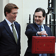 © Licensed to London News Pictures. 21/03/2012. Westminster, UK. British Chancellor of the Exchequer George Osborne holds his red ministerial box as he poses for pictures with Danny Alexander outside 11 Downing Street in London, on March 21, 2012. The Chancellor is expected to raise the amount of money people can earn before income tax takes hold and impose a new levy on the purchase of expensive homes. Photo credit : Stephen SImpson/LNP