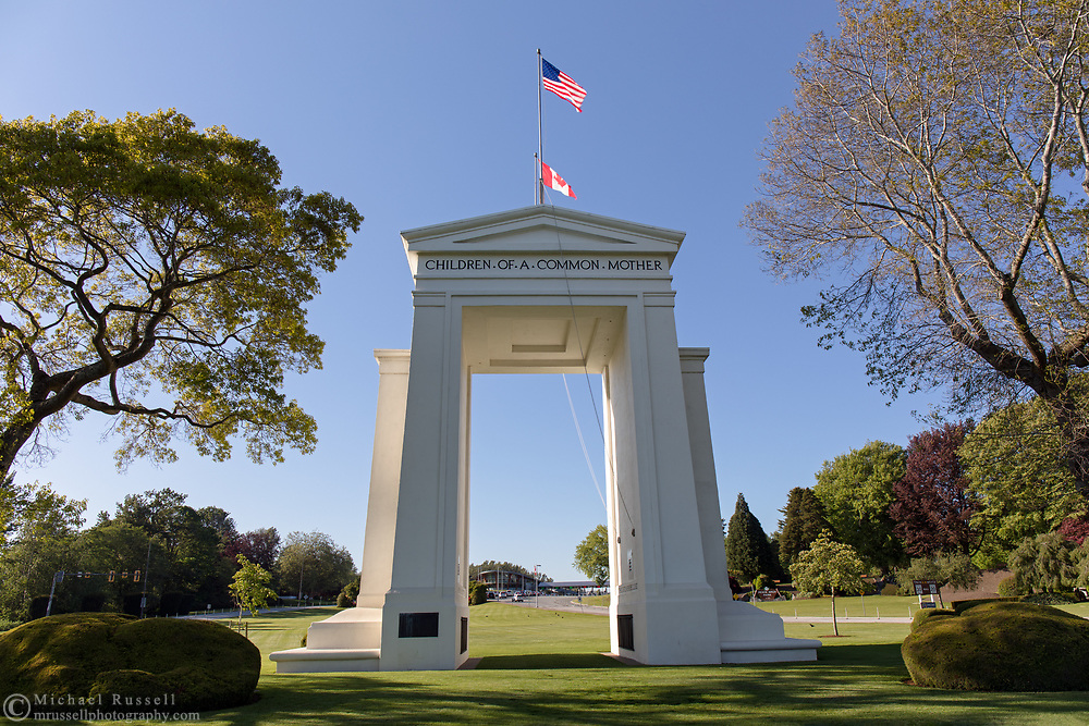 """The Peace Arch (1921) looking towards Canada.  Photographed from Peace Arch Historical State Park in Blaine, Washington State, USA.  The Peace Arch was built in 1921 to commemorate the 100 year anniversary of treaties at the end of the War of 1812 between the USA and Great Britain. One side states """"Children Of A Common Mother"""", the other """"Brethren Dwelling Together In Unity""""."""