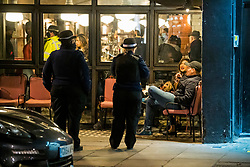 © Licensed to London News Pictures. 25/09/2020. London, UK. Police officers ask members of the public to leave a bar on Portobello Road in Notting Hill, west London, at 10pm when a curfew comes in to place as part of new restrictions intended to prevent the spread of COVID-19. Photo credit: Ben Cawthra/LNP