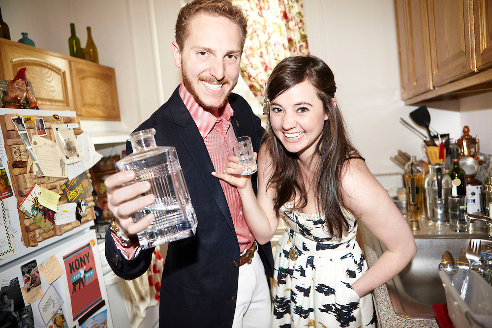 Lifestyle image of fun young couple having alcoholic drink inside kitchen