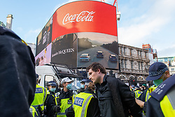 © Licensed to London News Pictures. 19/12/2020. London, UK. Police search a man after he was arrested for allegedly being in possession of a knife in Piccadilly Circus. Protesters have gathered in central London for an anti-lockdown demonstration. Photo credit: Peter Manning/LNP