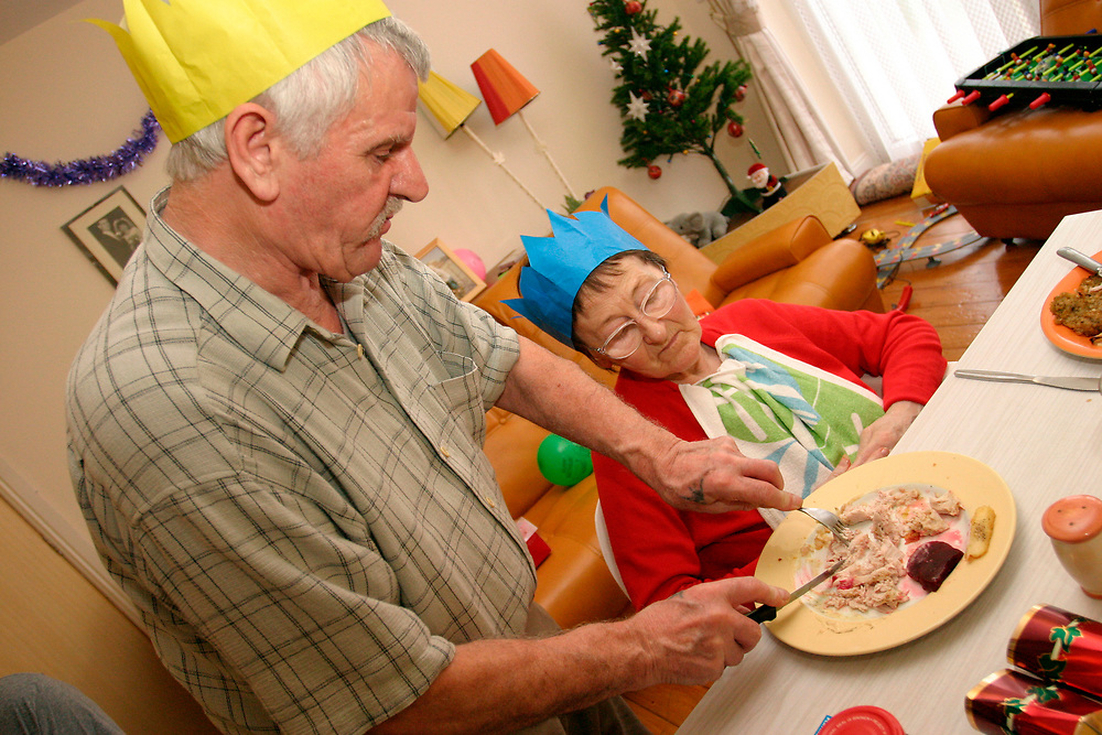 Elderly man helping his disabled wife with her Christmas dinner UK