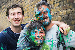 London, August 30th 2015. Already covered in paint and coloured powder, three friends pose for the camera as revellers await the start of the Notting Hill Carnival.