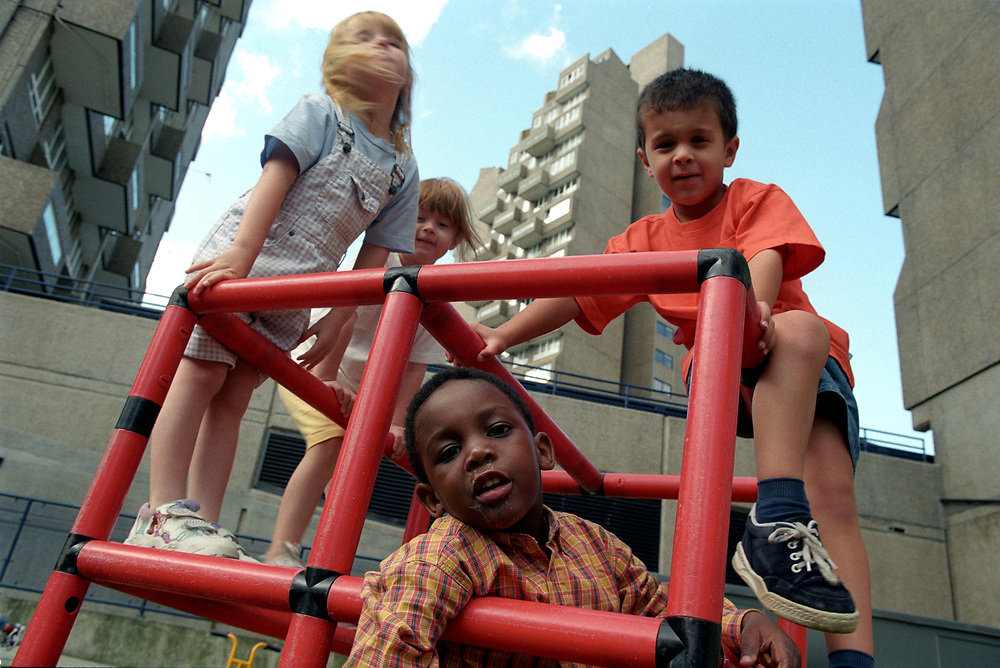 Young children playing at open air nursery on housing estate in London,