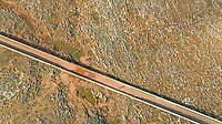 Aerial view of road crossing arid terrain at Balears Island, Spain.