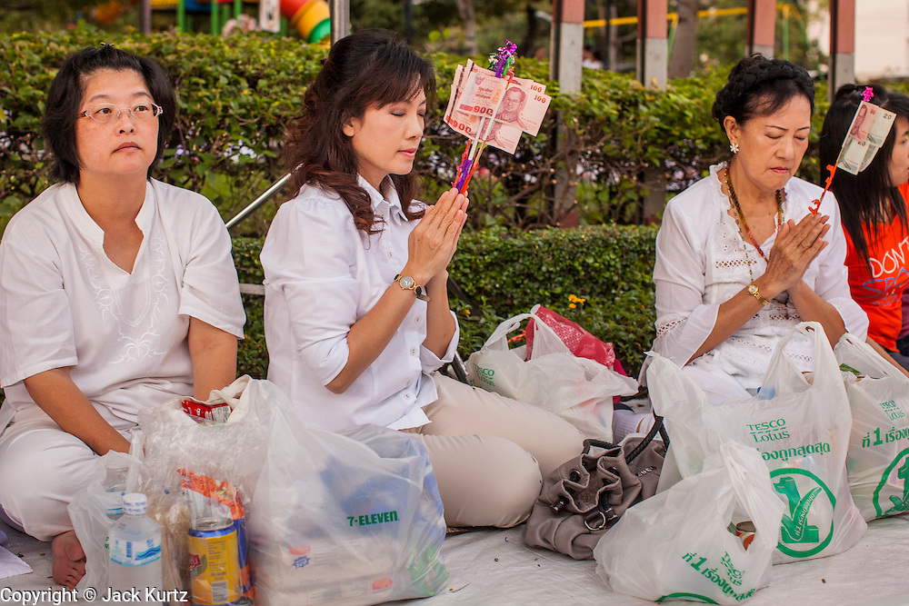 20 OCTOBER 2012 - BANGKOK, THAILAND: Women pray for peace in southern Thailand during a special alms giving ceremony in Bangkok. More than 2,600 Buddhist Monks from across Bangkok and thousands of devout Thai Buddhists attended the mass alms giving ceremony in Benjasiri Park in Bangkok Saturday morning. The ceremony was to raise food and cash donations for Buddhist temples in Thailand's violence plagued southern provinces. Because of an ongoing long running insurgency by Muslim separatists many Buddhist monks in Pattani, Narathiwat and Yala, Thailand's three Muslim majority provinces, can't leave their temples without military escorts. Monks have been targeted by Muslim extremists because, in the view of the extremists, they represent the Thai state.    PHOTO BY JACK KURTZ