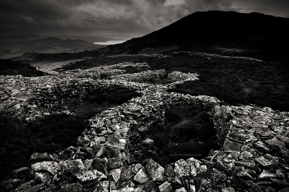From my book Nant Gwrtheyrn - Y Swyngyfaredd (The Enchantment)<br /> <br /> This is the impressive Iron Age hill-fort of Tre'r Ceiri, looking towards neighbouring Yr Eifl and on towards Nefyn and the Llyn. The hillside is very exposed and it's hard to imagine why people would settle this side of the hill! It would certainly get more sunlight, but would also face the prevailing winds and rain. However, its sheer size (approximately 150 huts) and condition impressed me greatly.