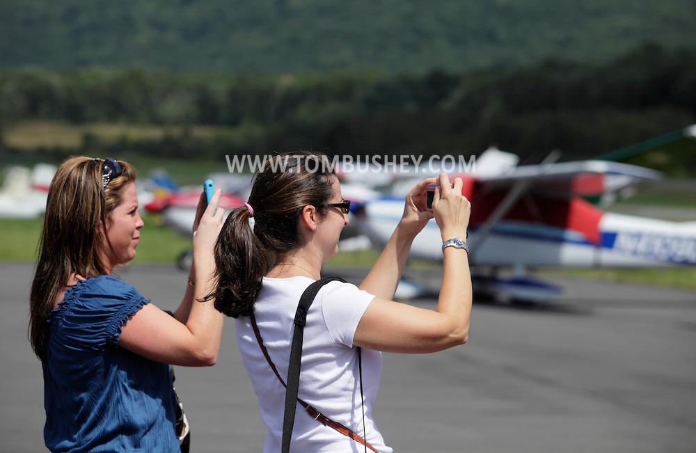 Wurtsboro, NY - Two women take photographs of planes at Wurtsboro Airport on Aug. 30, 2009.