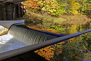 Water cascades over a roller dam on the Eau Claire River with vivid fall colors reflecting in southern Bayfield County, Wisconsin. The structure in the foreground is a manual lock system, one of only a few in the state.