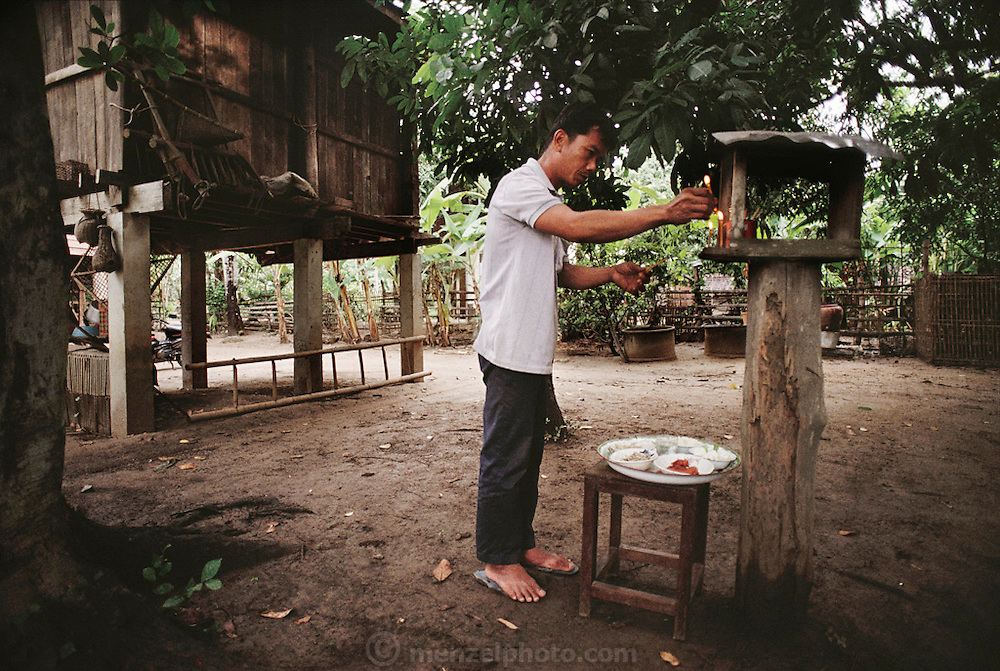 Boontham Khuenkaew places an offering of cucumbers, red pork, bamboo shoot stew, shrimp-paste, and rice before the spirit house in his yard. Spirit houses are the abodes of the many spirits that Thais regard as integral parts of the land. Because the spirits have the power to cause trouble, Boontham periodically placates them by lighting candles and placing a good meal there. He puts a little rice on the ground, and adorns the house with flowers. Thailand. The Khuenkaew family lives in a wooden 728-square-foot house on stilts, surrounded by rice fields in the Ban Muang Wa village, outside the northern town of Chiang Mai, in Thailand. Material World Project.