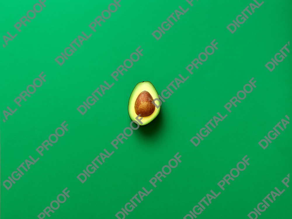 Avocado with seed isolated in green background viewed from above - flatlay look