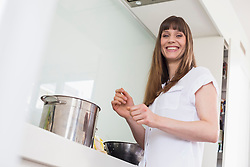 Portrait mid adult woman cooking in kitchen, smiling