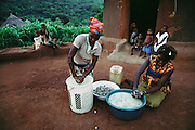 Village women outside their round house making traditional beer from the fruit of the marula tree in Tshamulavhu Village, Venda, South Africa.