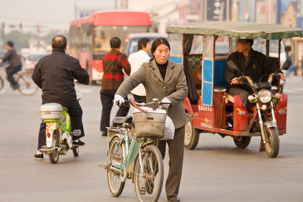 Suzhou, Jiangsu province, China, Asia - Woman with bicycle crossing the street in the chaotic traffic of Suzhou.