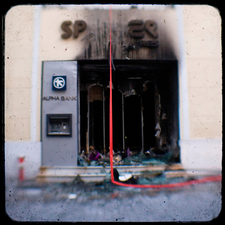 """Burned """"Sprider"""" shop at Ermou street located in the main shopping area of Athens.<br /> The killing of the 15 year old boy Alexandros Grigoropoulos by a policeman resulted in widespread riots that altered the city landscape. When I walked in the streets of my town the day after the riots I instantly forgot the image I had about Athens, that of a bustling, peaceful, energetic metropolis and in my mind came the old photographs from WWII, the civil war and the students uprising against the dictatorship. Thus I decided not to turn my digital camera straight to the destroyed buildings but to photograph through an old camera that worked as a filter, a barrier between me and the city."""