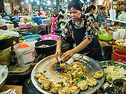 01 JUNE 2016 - SIEM REAP, CAMBODIA:  A vendor makes fried noodles in the Siem Reap market. There are growing concerns that spot food shortages, especially of fish, the Cambodians main source of protein, could become worse if the coming rainy season doesn't bring relief from the drought that has gripped Cambodia for the last two years.          PHOTO BY JACK KURTZ