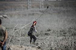 July 21, 2017 - Gaza, Jabalia, Gaza - A Palestinian protester uses a sling to hurl a stone towards Israeli troops during clashes with Israeli security forces near the border fence east of Jabalia refugee camp on July 21, 2017 in protest against new Israeli security measures implemented at Al-Aqsa mosque complex, known to Jews as the Temple Mount, in Jerusalem. The new security measures include metal detectors, security cameras, and barring men under 50 from entering the Old City for Friday Muslim prayers, following an attack that killed two Israeli policemen the previous week. (Credit Image: © Nidal Alwaheidi/Pacific Press via ZUMA Wire)