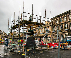 """Edinburgh, Edinburgh, Scotland, United Kingdom, 05 December 2019, Trams to Newhaven: Work is underway in Constitution Street to reroute underground utility pipes and to remove the historic statue of Robert Burns by sculptor D.W. Stevenson RSA erected in 1898 which was cast at the foundry of J.W. Singer and Sons, which is now beiung covered in scaffolding. Banners have been put on the barrier fencing stating """"Any Questions?"""",  """"We're supporting local businesses throughout the works"""" and """"Thank you for your patience"""".  The work is expected to take around 3 years taking the first passengers along the 2.91 mile extension in 2023."""