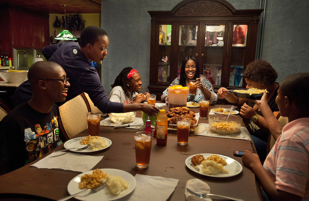 Terri L. Jenkins, standing, serves food as her wife Tammy Peay leads her family in dinner, including Tammy's biological son David Grant, 16, far left, and foster children Tyra Watson, 14, Alexis Buchanan, 15, and Jasmine Williams, 17, in Easton, Pa., Sept. 8, 2011.