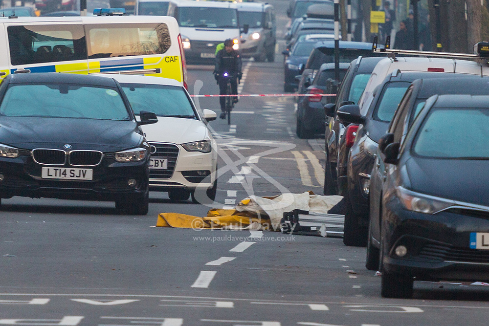 What appears to be a forensic tent lies on Malden Road as police man a cordon surrounding the scene on Malden Road where a man was stabbed to death. Camden, London, February 21 2018.