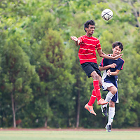 Afariss Khan (#8) of Millenia Institute heads the ball against Aehanz Amran (#4) of Yishun Junior College during the group stage match of the National 'A' Division Football Championship at Meridian Junior College on April 1, 2014, in Singapore.