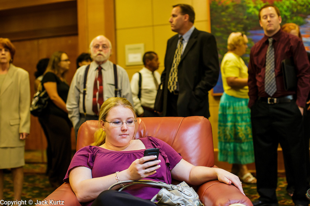 30 JULY 2012 - PHOENIX, AZ:    DAMARIS ROGERS, from Mesa, AZ, checks her smart phone before looking for a job at the Phoenix Job Fair in Phoenix, AZ. She said she was looking for a clerical position. The job fair was sponsored by National Career Fairs, which organizes job fairs across the US. Several hundred people attended the job fair, with some arriving hours before it started. More than 30 employers and prospective employers were conducting interviews at the job fair. There were also resume coaches and educational institutions on site. Arizona is still grappling with the recession. The state's unemployment rate is stuck at 8.2% and the Phoenix metropolitan area has one of the highest home foreclosure rates in the United States.   PHOTO BY JACK KURTZ