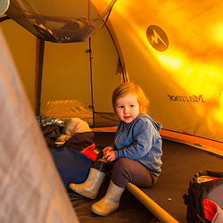 A young girl snacks in a tent on Lanes Island in Casco Bay. Yarmouth, Maine.