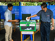 07 AUGUST 2016 - BANGKOK, THAILAND:  A man drops his ballot into the ballot box at a polling place at Wat That Thong in Bangkok. Thais voted Sunday in the referendum to approve a new charter (constitution) for Thailand. The new charter was written by a government appointed panel after the military coup that deposed the elected civilian government in May, 2014. The charter referendum is the first country wide election since the coup.     PHOTO BY JACK KURTZ
