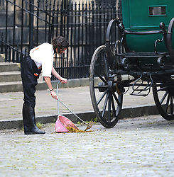 """Moray Place in Edinburgh's Georgian old town was turned into 19th century London for Julian Fellowes' new ITV show """"Belgravia"""".<br /> <br /> Pictured: An extra clears up the horse manure from the cobbles<br /> <br /> Alex Todd 