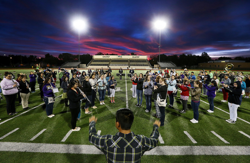 The Senior High band warms up as the sun begins to light the morning sky during practice Monday at Grand Island Senior High. Senior High will be defending it's Class AA parade performance, superior rating in field contest, and best overall performance titles at Harvest of Harmony in less than a week. (Independent/Matt Dixon)
