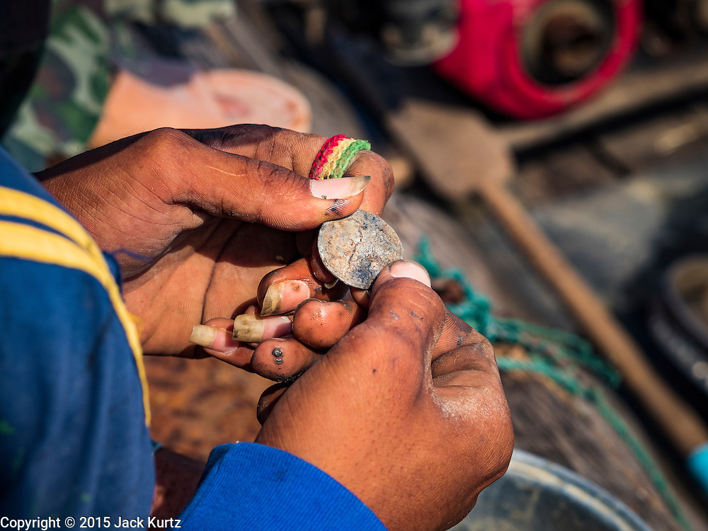 14 OCTOBER 2015 - BANGKOK, THAILAND:  A spotter looks at an old coin brought up from the bottom of the Chao Phraya River in Bangkok. Divers work in two man teams on small boats in the Chao Phraya River. One person stays in the boat while the diver scours the river bottom for anything that can be salvaged and resold. The divers usually work close to shore because the center of the river is a busy commercial waterway with passenger boats and commercial freight barges passing up and down the river all day long. The Chao Phraya is a dangerous river to dive in. It's deep, has large tidal fluctuations, is fast flowing and badly polluted. The divers make money only when they sell something.   PHOTO BY JACK KURTZ