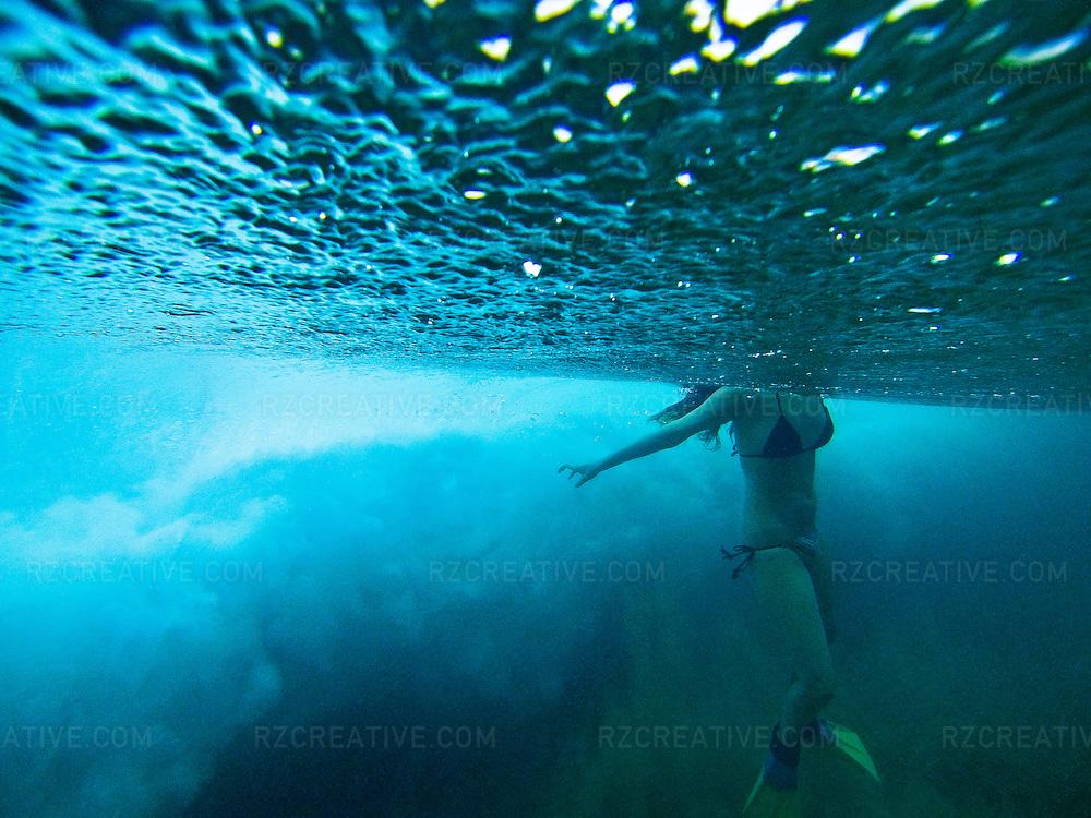 Underwater photo of an woman in a bikini wearing swim fins.