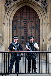 © Licensed to London News Pictures. 28/03/2017. London, UK. Armed police stand at an entrance to Parliament. Security around London has been increased following Khalid Masood's terrorist attack and the killing of PC Keith Palmer on 22 March. Photo credit : Tom Nicholson/LNP