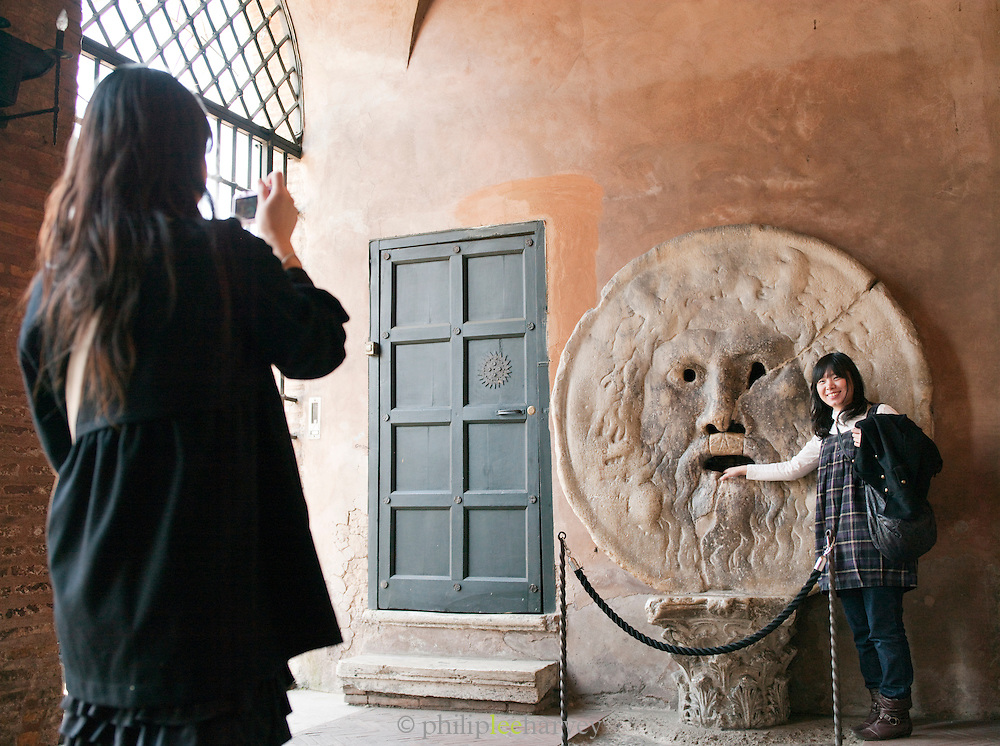 Tourists at the Mouth of Truth at the Basilica di Santa Maria in Cosmedin, Rome, Italy