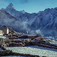 Smoke rises from houses in Khunde village in the Khumbu region of Nepal's Himalaya. Sacred mount Ama Dablam in background. 1979 photo.