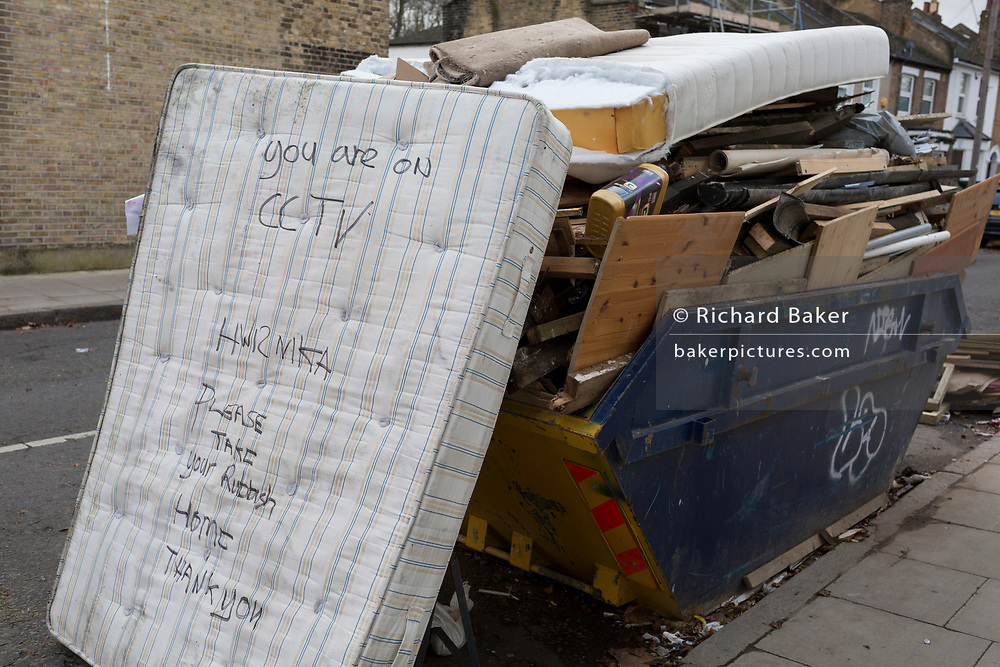 A dumped mattress next to a skip full of licensed waste, seen on a nearby shop's CCTV camera which recorded the car's registration number while stopped on a residential street in East Dulwich, on 7th December 2019, in south London, England.