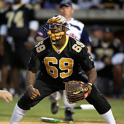 Apr 28, 2010; Metairie, LA, USA; Anthony Hargrove (69) plays catcher during the Heath Evans Foundation charity softball featuring teammates of the Super Bowl XLIV Champion New Orleans Saints at Zephyrs Field.  Mandatory Credit: Derick E. Hingle-US-PRESSWIRE.
