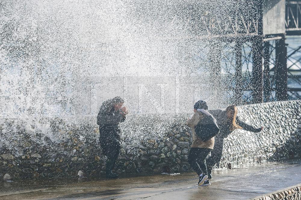 Brighton, UK. 21/11/2016, INDIA CONEY 17, BEZYA GEDIK 16 and YANA ROGER 16 get soaked as powerful waves are hitting the pontoon next to the Brighton Palace Pier. Photo Credit: Hugo Michiels